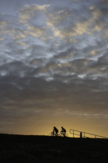 Silhouette people riding motorcycle against sky during sunset