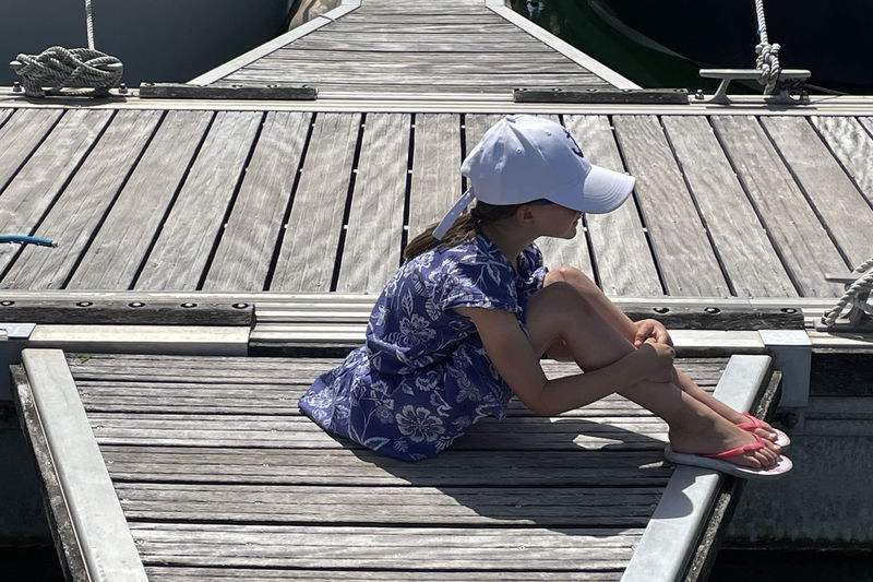 Full length of woman sitting on pier