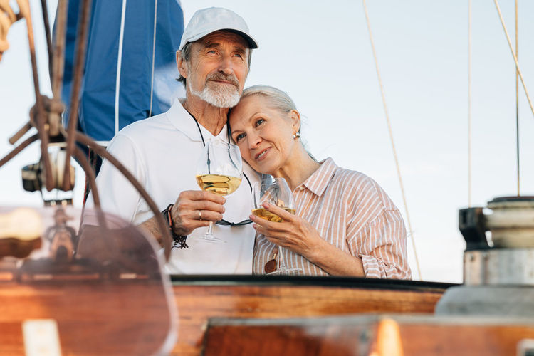 Senior couple holding wineglass standing on boat