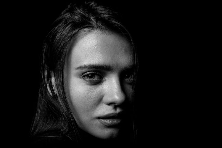 Portrait of a beautiful young girl. Black background for the woman. Low key. Parts of the human body. Expressive eyes. Black and white photography. Studio photo. Low Key Portrait Black Background Woman Blackandwhite