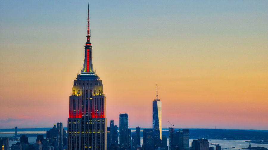 Empire state building and modern towers against clear sky at sunset