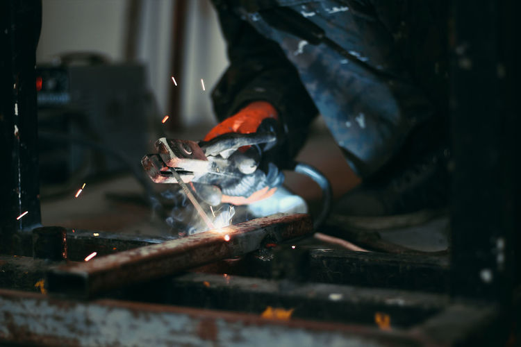 Low section of worker welding metal in workshop