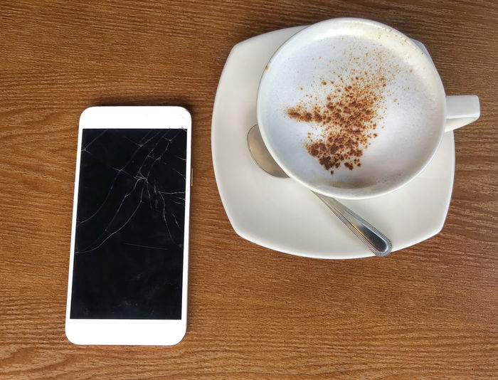 Mobile cracked tuchscreens for communications is brocken placed on a wooden table and coffee mugs in coffee shop Table Coffee Coffee - Drink Coffee Cup Refreshment Drink Mug Cup Still Life Food And Drink Wireless Technology Wood - Material Indoors  Directly Above Saucer No People Communication Frothy Drink Smart Phone Kitchen Utensil Crockery Tray