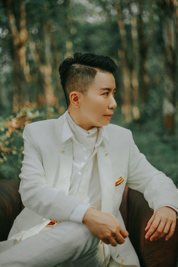 Young man wearing white suit on chair against trees