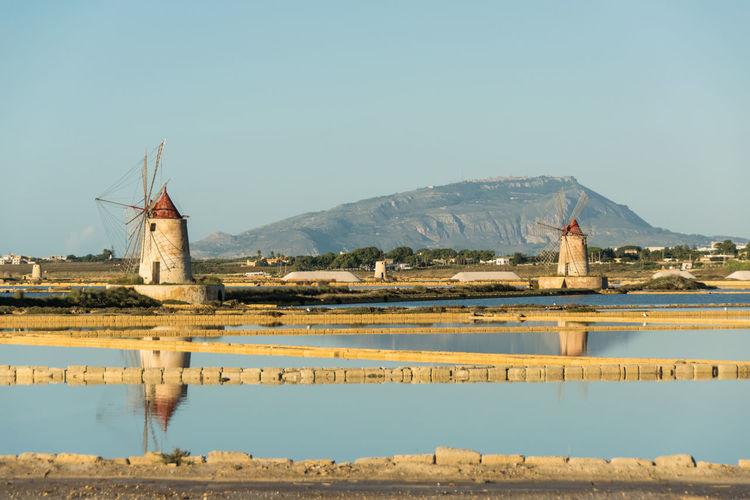 Traditional windmills by lake against clear sky