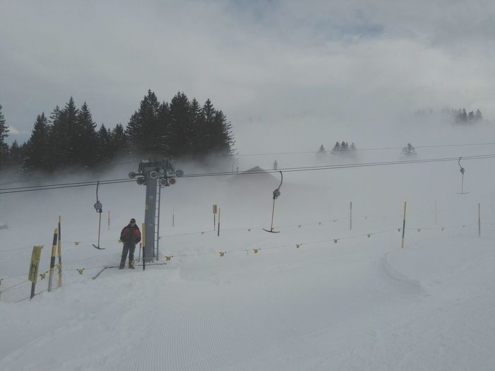.....with the Fog came the Mood ...Skilift Warden Standing Alone ...... One Person Standing And Waiting and the Chalet / Woods in the Background is Tenderly Caressed by the Mist... Up And Down Whitescale Tranquil Scene Trees Snow Skiing Snowtrack