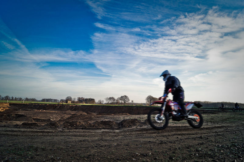 Person riding motocross on field against sky