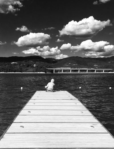 Lost In The Landscape Sky Pier Cloud - Sky Water Jetty Lake Nature Day Bird Outdoors Rear View Sitting Beauty In Nature Wood Paneling Swan Built Structure Real People Animal Themes Mountain