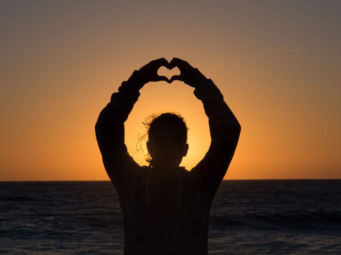 Silhouette man with heart shape against orange sunset sky