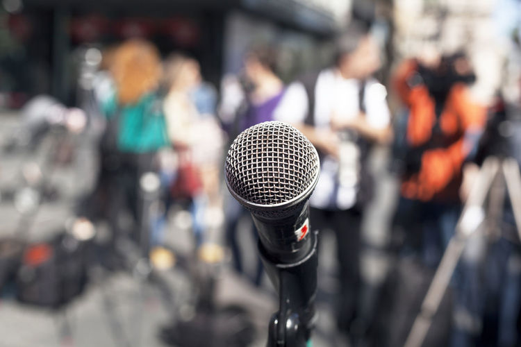 Close-Up Of Microphone Against People