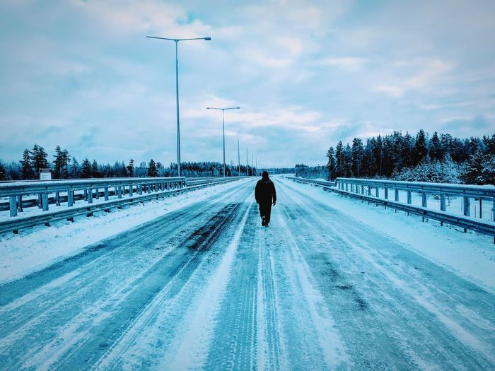Rear view of man on snow covered road