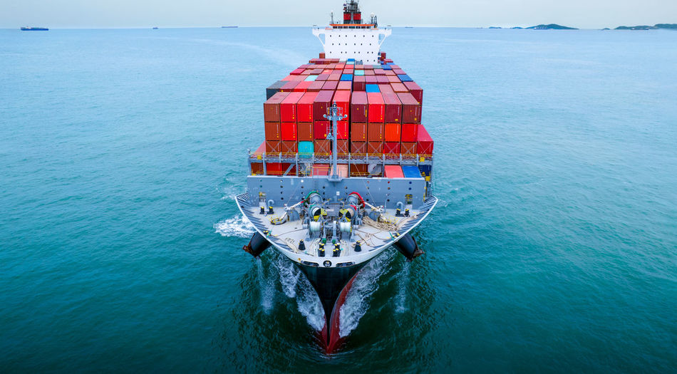 Aerial in front view of cargo ship with contrail in the ocean sea ship carrying container