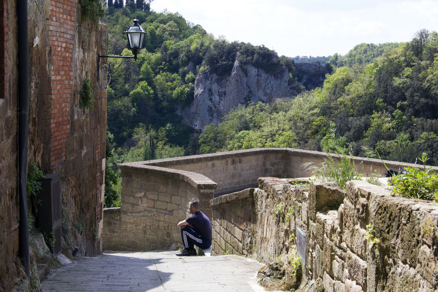 Pitigliano Italy Architecture Building Exterior Built Structure Casual Clothing Day Leisure Activity Lifestyles Men Mountain Nature One Person Outdoors Plant Real People Sitting Tree