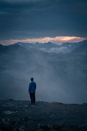 Rear View Of Man Standing On Mountain Against Cloudy Sky During Sunset