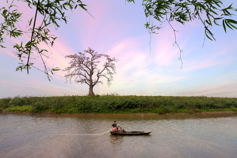 Man in boat on river against sky