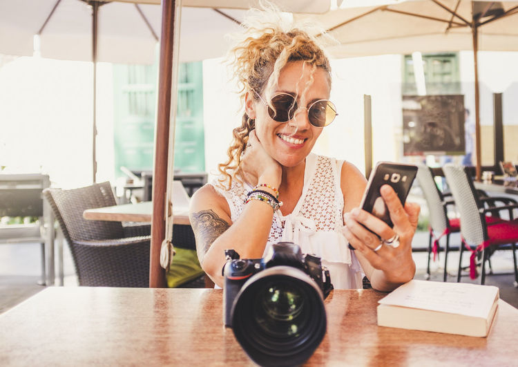 Smiling woman holding smart phone while sitting with camera at table