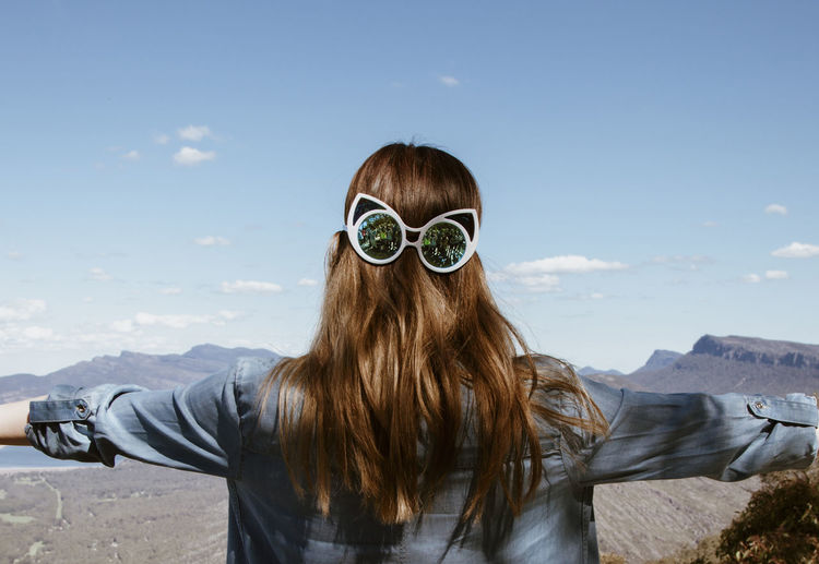 Rear view of woman wearing sunglasses against sky