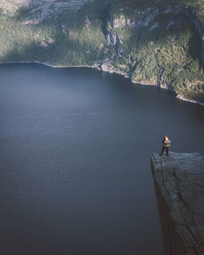 Man standing on cliff by sea