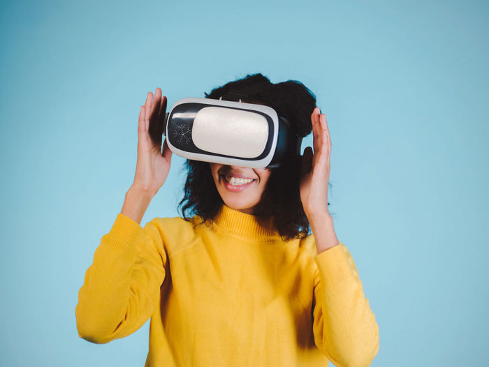 Smiling woman using vr glasses against blue background