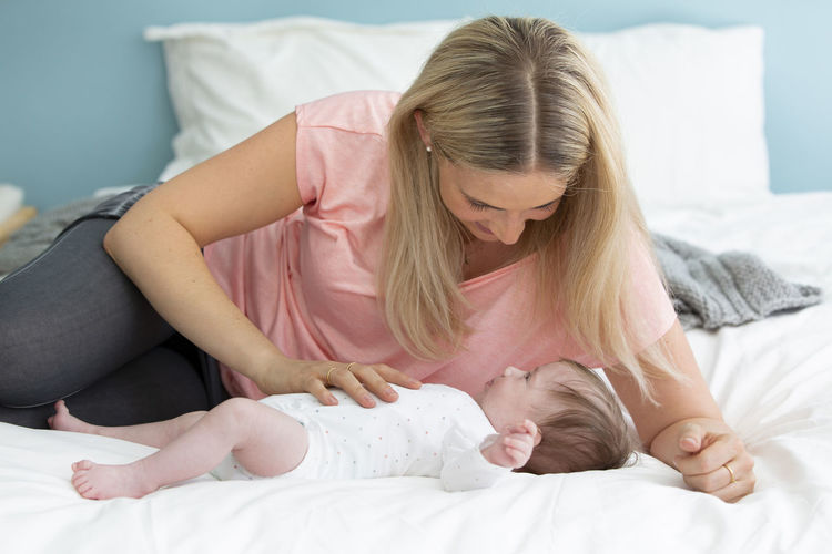 young, beautiful and blond mother with pink shirt is cuddling with her baby in bed Family Love Adult Babygirl Bed Bedroom Bonding Care Child Childhood Cuddling Daughter Domestic Room Family Females Furniture Hair Indoors  Innocence Lifestyles Lying Down Mother Mothersday Positive Emotion Real People Relaxation Togetherness Two People Women