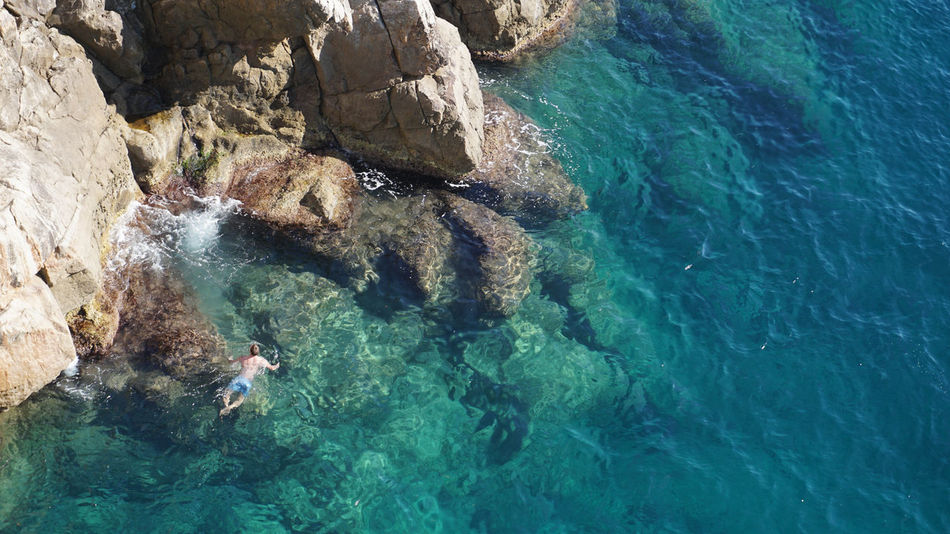 a man swimming in the sea near Dubrovnik, Croatia Cristal Clear Holiday Swimming Beauty In Nature Blue Crotia Dubrovnik High Angle View Lifestyles Nature Rock - Object Scenics Sea Sport Travel Destinations Water