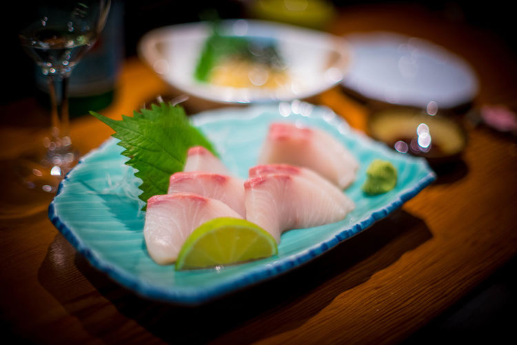 Ricciola fish in a Japanese restaurant. Ricciola Bowl Close-up Drink Food Food And Drink Freshness Garnish Glass Healthy Eating Indoors  Japanese Food Lemon No People Plate Ready-to-eat Refreshment Sashimi  Sashimi  Seafood Selective Focus Serving Size Still Life Table Wellbeing