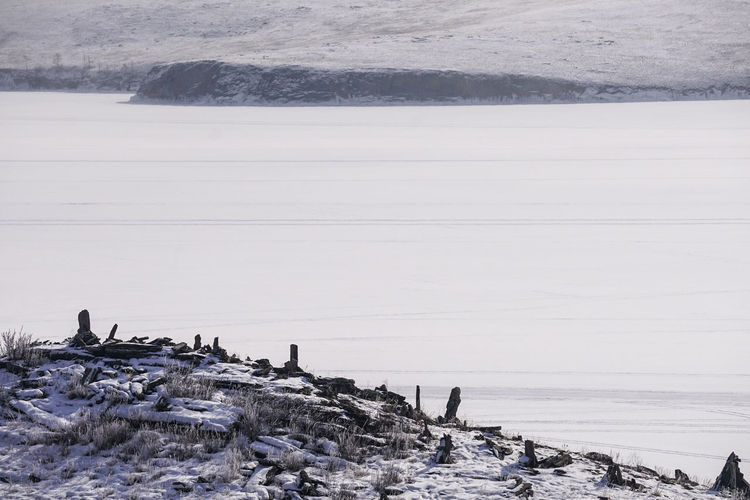 People on shore by sea against sky during winter