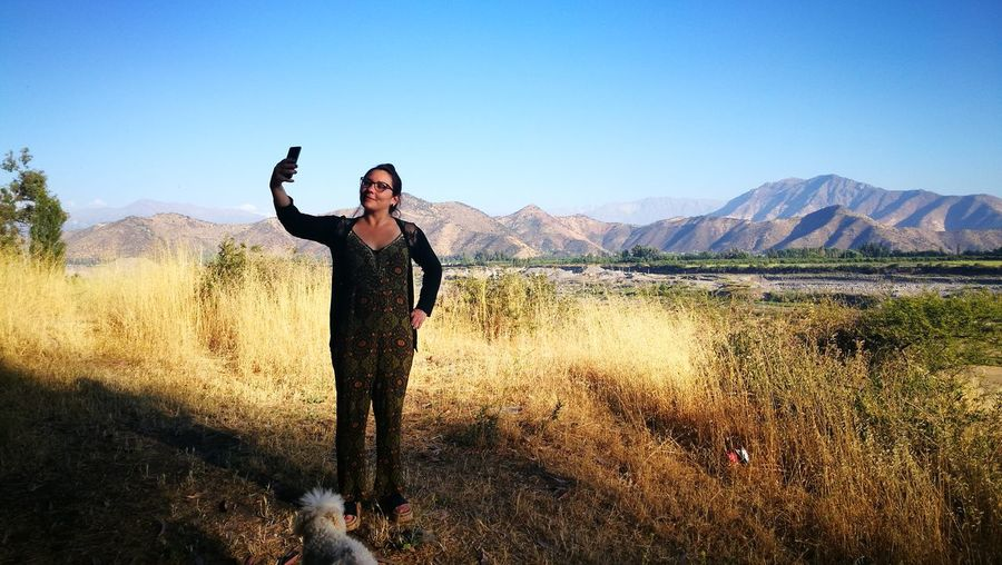 Full length of woman taking selfie while standing on field against mountains