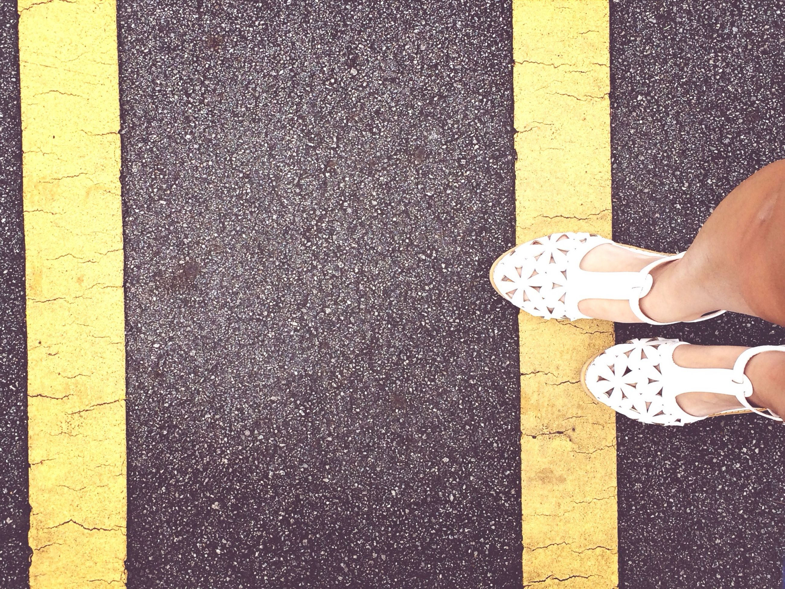 low section, person, yellow, shoe, lifestyles, street, standing, footwear, personal perspective, leisure activity, high angle view, part of, human foot, men, unrecognizable person, road