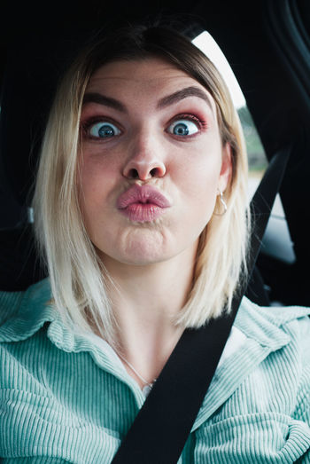 Close-up portrait of beautiful young woman making face while sitting in car