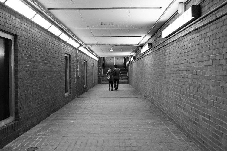 Rear view of people walking on corridor