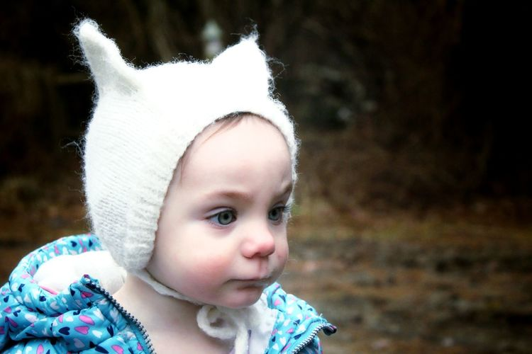 Close-up of cute baby girl in warm clothing looking away