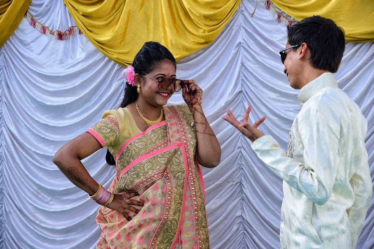 Young Couple Wearing Sunglasses While Standing Against Curtain