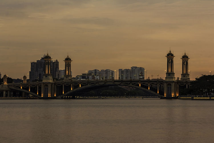 Bridge over river with buildings in background at sunset