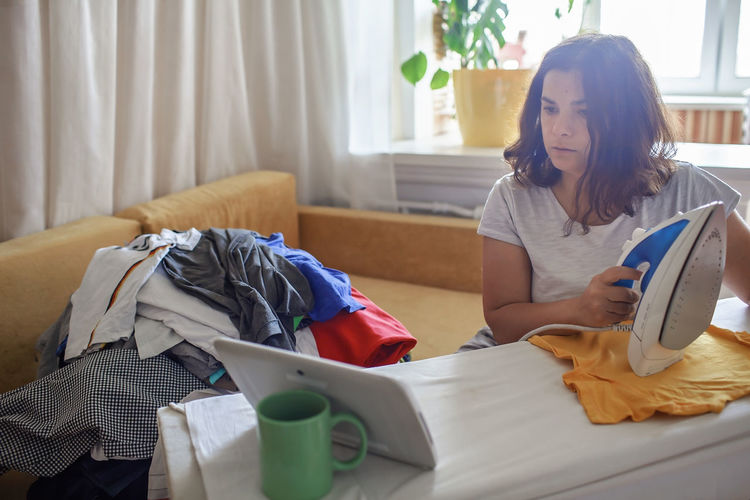 Midsection of woman holding mobile phone while sitting on bed at home