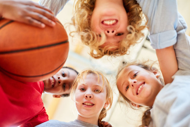 Low angle portrait of friends huddling in school basketball court