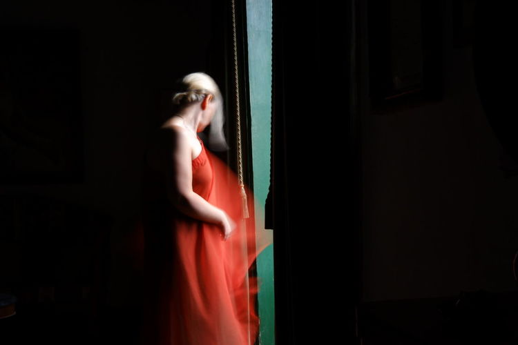 Side view of young woman standing in dark room