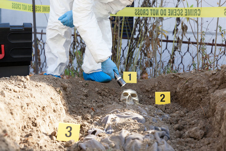 Forensic science specialist, holding a flashlight, working at a crime scene. Police investigation of a murder Working Human Body Part Forensic Science Forensics Forensic Specialist Investigator Police Detective Protective Workwear Evidence Marker Crime Scene Crime Criminal Skull Flashlight Homicide Investigation Corpse Dna Evidence Exhumation Murder FootPrint Digging