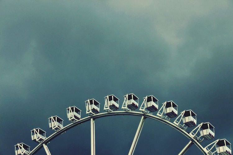 Low Angle View Of Ferris Wheel Against Cloudy Sky At Dusk