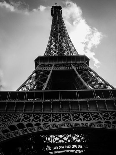 Low angle view of eiffel tower against cloudy sky