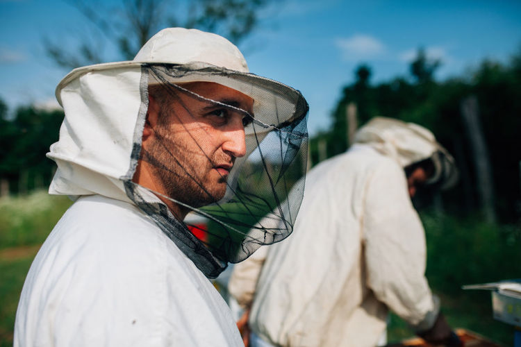 Side view of beekeepers standing by colleague on land