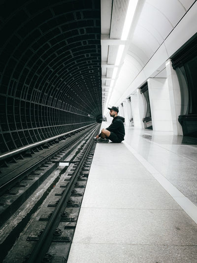 Man sitting at subway station platform