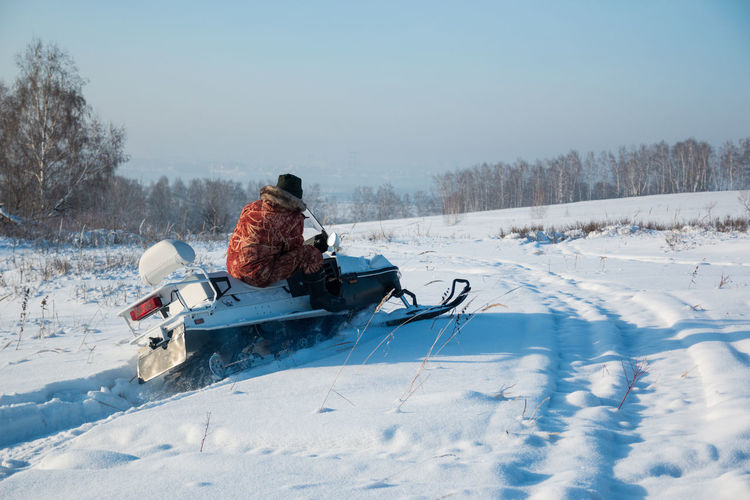 Rear view of person tobogganing on snow covered field against sky