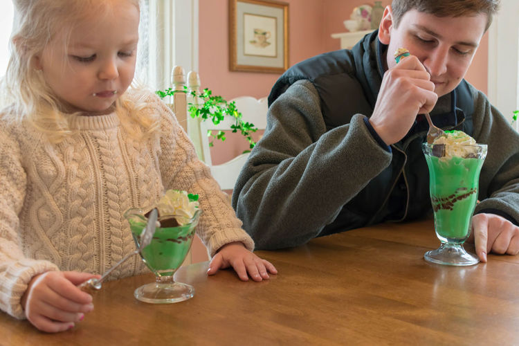 Siblings having ice cream while sitting at table in cafe