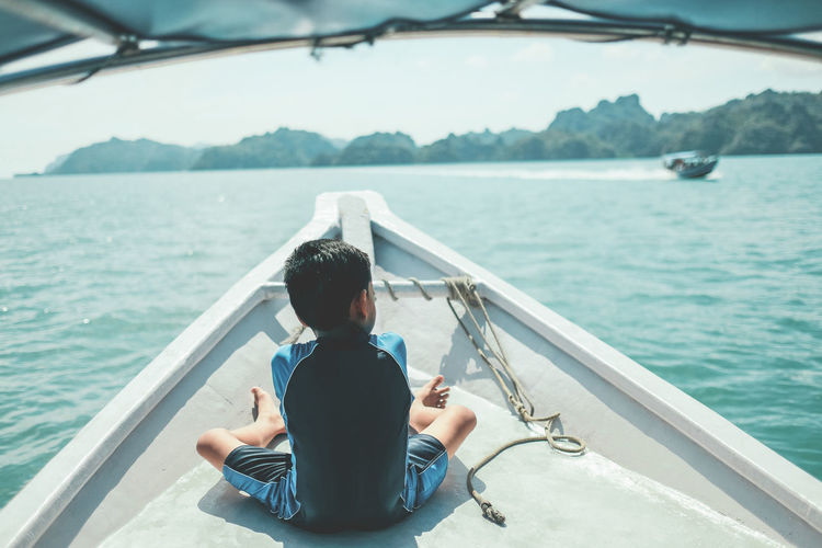 Rear view of man sitting on boat sailing in sea