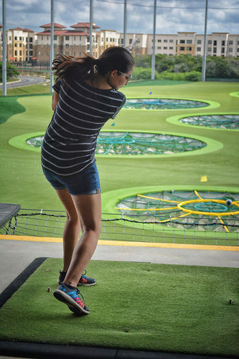 Full length rear view of woman playing golf