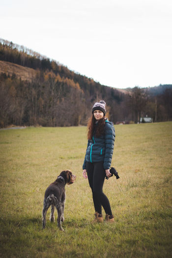 Full length portrait of woman with dog on field against sky
