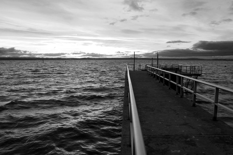 Friedrichshafen Lake Of Constance Bodensee Monochrome Black And White Blackandwhite Sunset Water Cloud - Sky Sky Sea Scenics - Nature Beauty In Nature Nature Tranquil Scene Railing No People Tranquility Beach Transportation Mountain Land Day Outdoors Pier Nautical Vessel Long