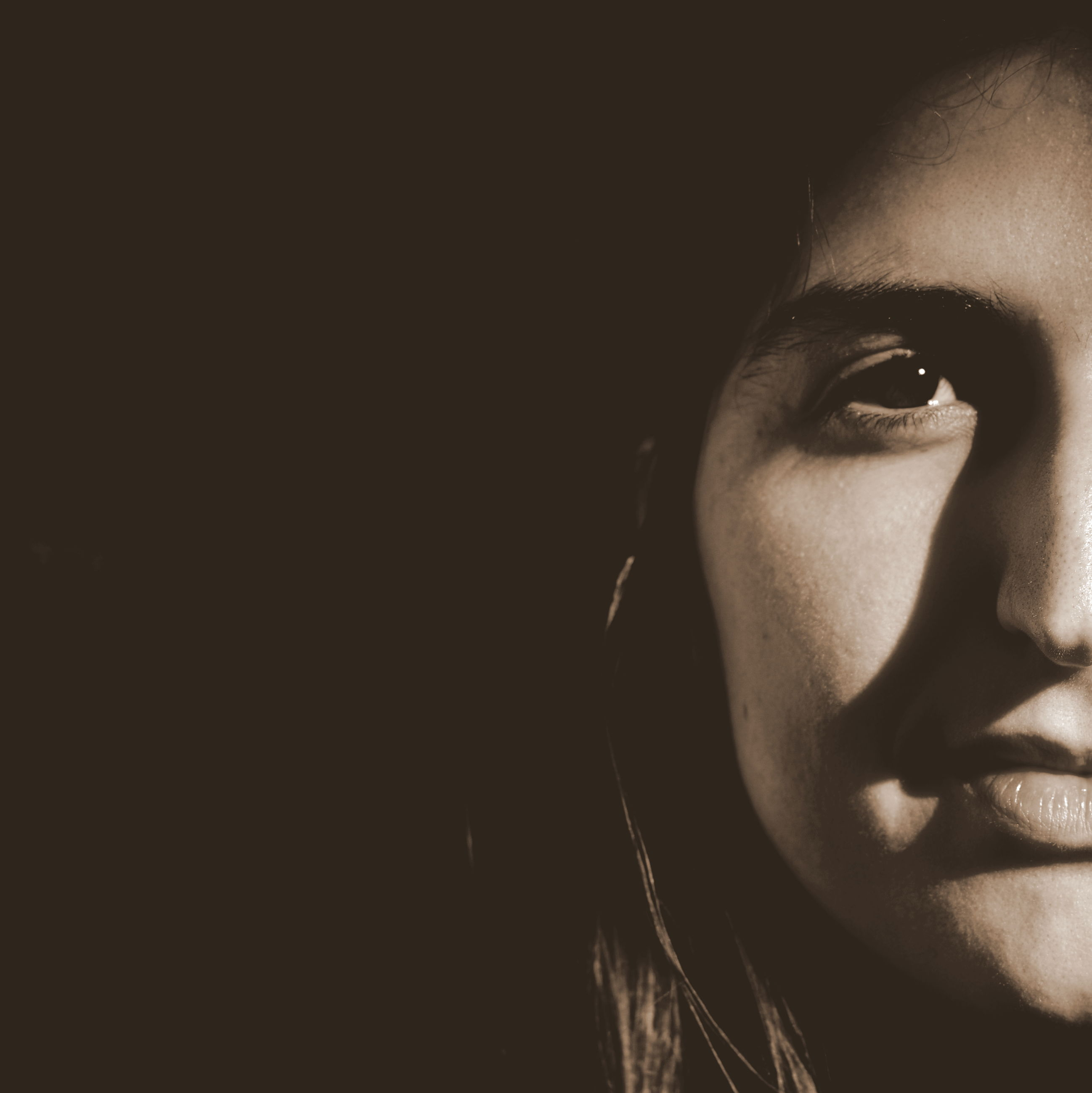 studio shot, black background, headshot, young adult, human face, portrait, close-up, looking at camera, front view, person, young women, lifestyles, copy space, indoors, head and shoulders, serious, contemplation