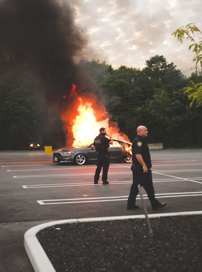 People standing by fire on road against trees